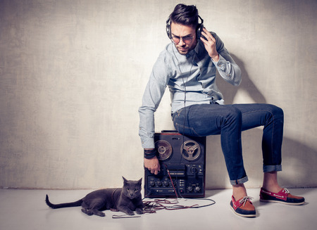 playback: handsome man and cat listening to music on a magnetophone against grunge wall