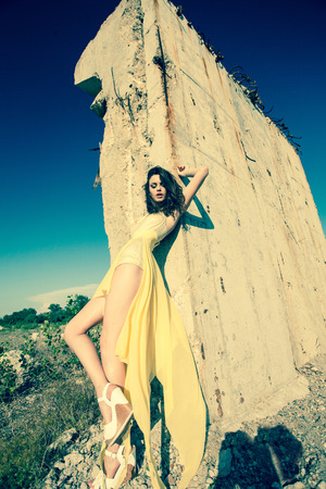 scenary: beautiful model in green dress posing in grunge location Stock Photo