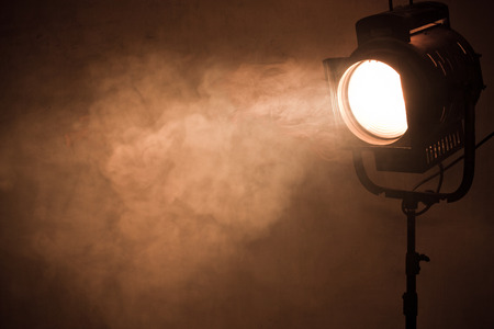 at the theater: theater spot light with smoke against grunge wall