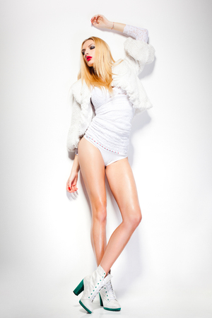 sexy fashion woman model dressed in white wearing sunglasses posing glamourous in the studio