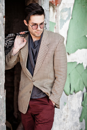 sexy fashion man model dressed vintage elegant holding a bag posing outdoor Zdjęcie Seryjne