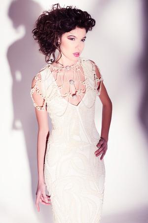 beautiful woman model posing in elegant pearl dress in the studio Zdjęcie Seryjne