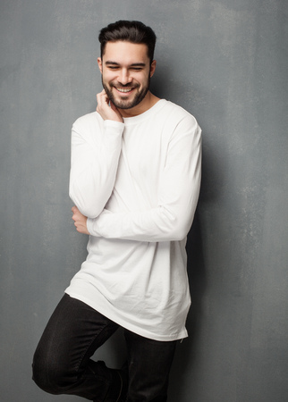 sexy fashion man model in white sweater, jeans and boots smiling Zdjęcie Seryjne
