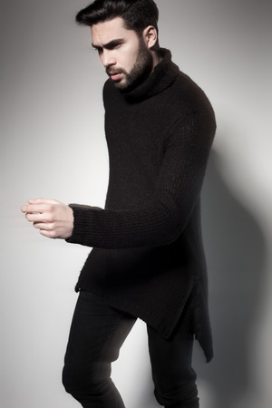 sexy sweater: sexy fashion man model in black sweater, jeans and boots posing dramatic