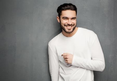 hombres negros: modelo atractivo hombre de moda en el suéter blanco, pantalones vaqueros y botas sonriendo contra muro
