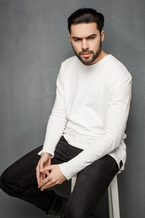 sexy fashion man model in white sweater, jeans and boots posing dramatic Zdjęcie Seryjne