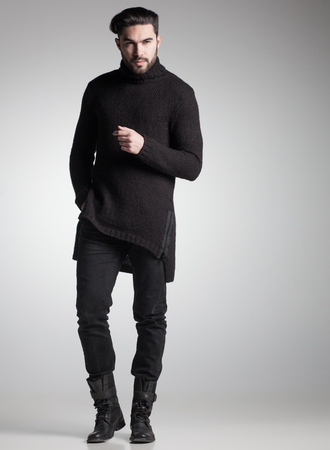 sexy fashion man model in black sweater, jeans and boots posing dramatic photo