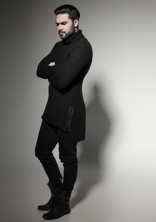 black male: sexy fashion man model in black sweater, jeans and boots posing dramatic