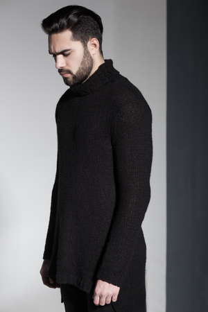 young male: sexy fashion man model in black sweater, jeans and boots posing dramatic