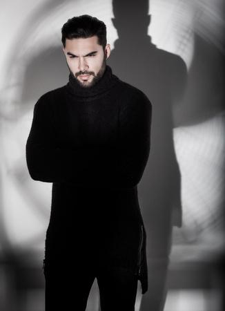 sexy Mode-Mann-Modell in schwarzen Pullover, Jeans und Stiefel dramatischen aufwirft