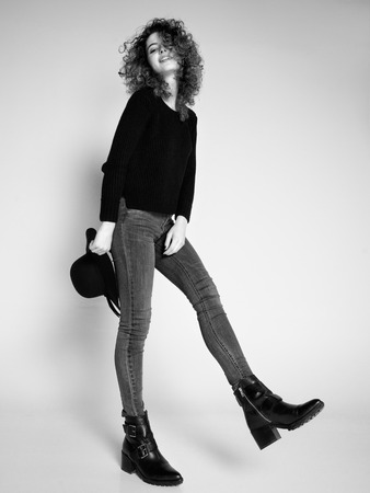 pretty woman posing in denim pants and boots and black hat