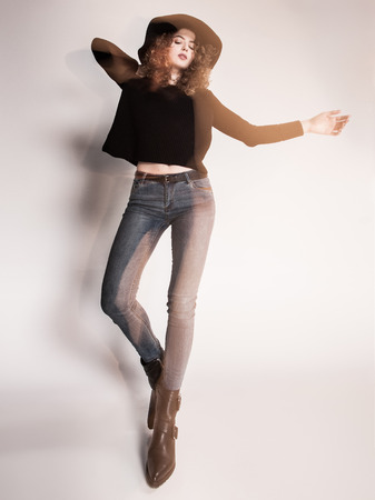 female model: pretty woman posing in denim pants and boots and black hat - intentional motion blur