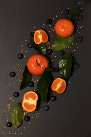 Tangerines with blueberries on gray background
