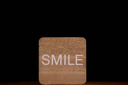 Smile on wood plate. (Black background)