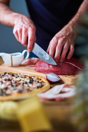 cut: Close-up of mans hands cut beef with knife on board. Sauce-boat, half onion and cooked pizza lying on table too. Stock Photo