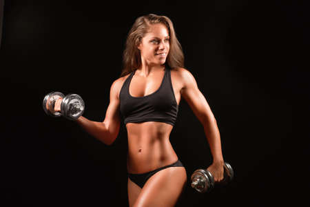 Closeup photo of a sports woman portrait wearing black sportswear over dark lifting dumbell Zdjęcie Seryjne