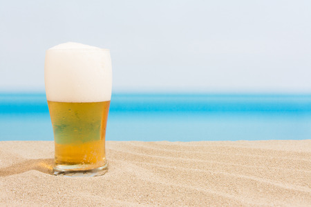 liquid summer: Beer on the beach Stock Photo