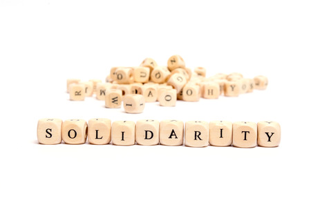 solidaridad: palabra con los dados en el fondo blanco solidaridad