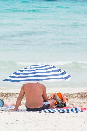 ordinary: ordinary people under beach umbrella