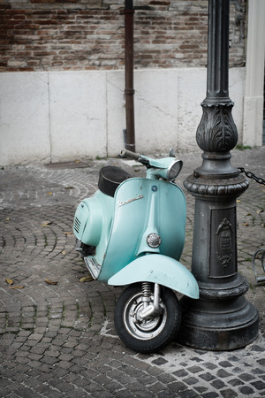 FANO, ITALY - NOVEMBER 16, 2014: The Vespa, old italian scooter made by Piaggio, parked on old street in Fano, Italy.