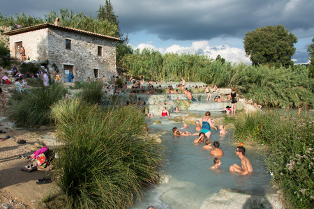hydrothermal: SATURNIA, ITALY - August 24, 2015: tourists swimming and relaxing in hot springs in Saturnia at Mulino, this spa world famous has  natural waterfalls, near the city of  Manciano, in tuscan