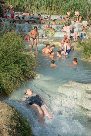 therapy geothermal: SATURNIA, ITALY - August 24, 2015: tourists swimming and relaxing in hot springs in Saturnia at Mulino, this spa world famous has  natural waterfalls, near the city of  Manciano, in tuscan