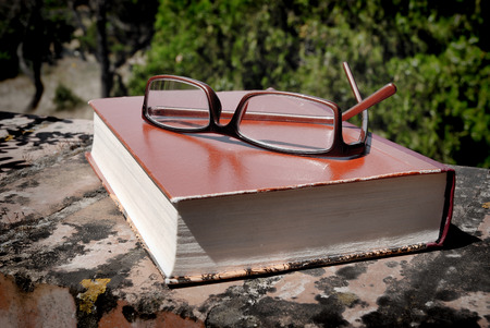 book and glasses on the wall outdoors Stock Photo