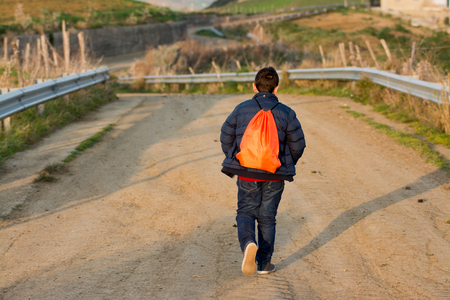 rough road: Teenager walking away on rough road. Concept of escape and adventure