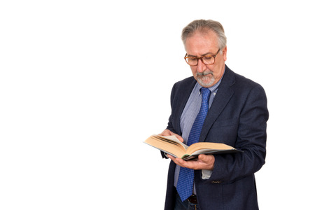 the elderly tutor: Senior teacher standing reading a book, isolated on white background. Education concept Stock Photo