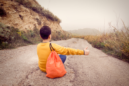 Teenager sitting on the street, waiting for the passage of a car Stock Photo