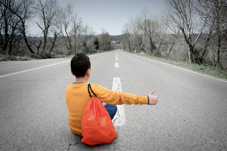 autonomia: Teenager sitting on the road, waiting for the passage of a car
