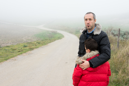 Concept of family escaping.  Father and son in a mountain road with fog. Scene with actors Stock fotó