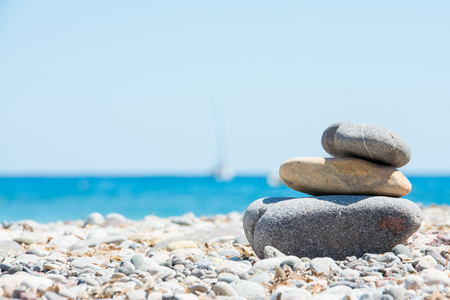 Relaxing in summer  concept. Stones on the beach with boat on background Mallorca