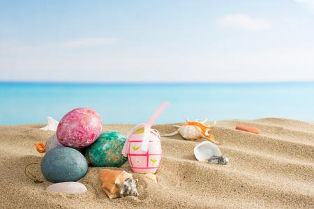 Pasen op het strand achtergrond. Eieren op het zand door de oceaan. Vakantie en reizen, lenteconcept Stockfoto