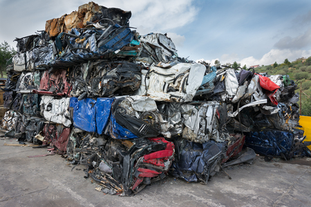 scrapyard: Cars in junkyard,  pressed and packed for recycling.