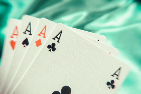 The combination of playing cards poker casino. Four aces on green background