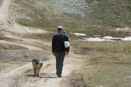 man walking with his dog in the mountains
