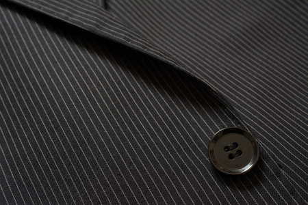 Detail der Nahaufnahme des Anzugsknopfes auf Stift gestrippt Tuch Schneiderei Hintergrund Standard-Bild