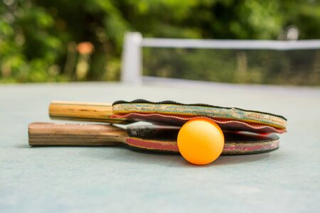 paddles and ball on retro  blue wooden background. Rackets ruined by time 免版税图像