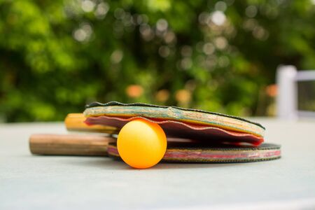 Ping pong paddles and ball on retro  blue wooden background. Rackets ruined by time