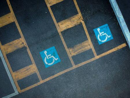 Disabled blue parking sign painted on dark asphalt. Empty handicapped spaces on black.