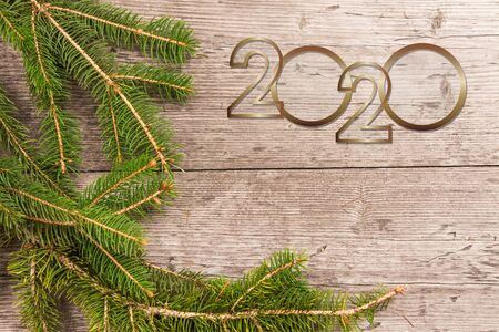 new year 2020. Christmas greeting card. Branch of fir on wooden background and copy space