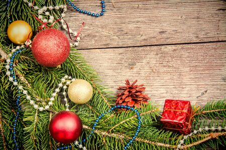 Christmas background with decorations and gift boxes on wooden board, empty space for text