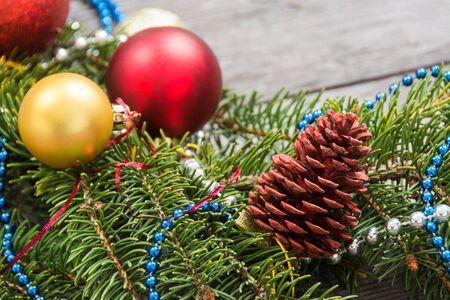 Christmas decoration baubles with branches of fir tree on wooden background