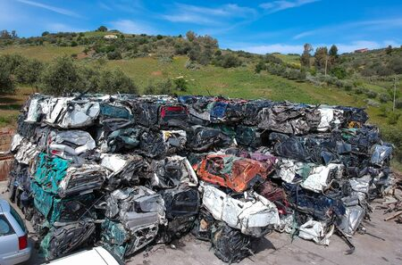 Cars in junkyard, pressed and packed for recycling. Car recycling
