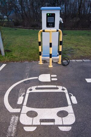 Electric vehicle charging station sign in a parking bay  Imagens