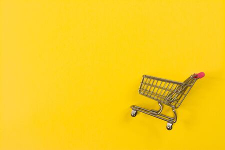 Fast shopping cart on yellow background with copy space for text