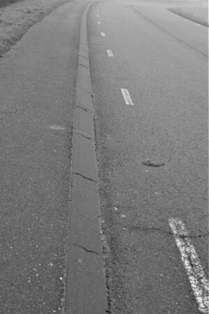 White stripes on the road along curb black and white