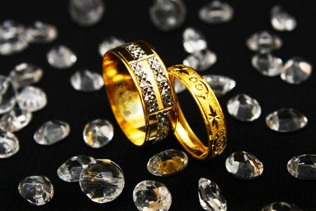 Reflection of bride and groom on a pair of gold couple ring surrounded with many crystals.