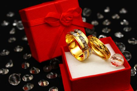 A pair of couple ring in small red box surrounded with crystals. Stock Photo